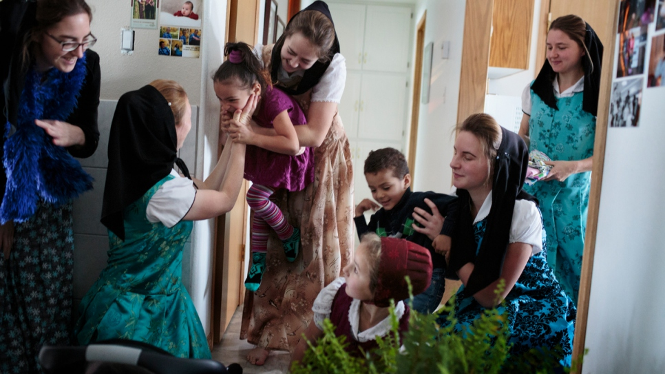 Members of the Hutterite community play with Raghad (left) and Ali.