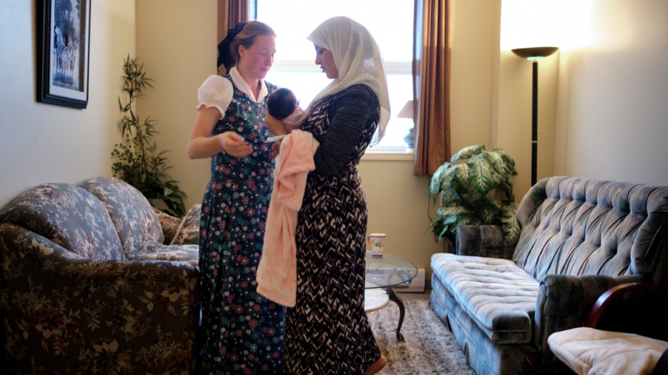 Elaine Hofer (left) helps Najwa Hussein to care for her newborn daughter, Janna.