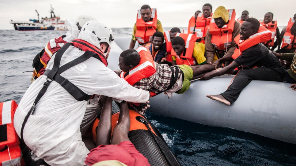 MOAS Search and Rescue Crew transfer people off a dinghy during a rescue operation in the  Mediterranean Sea.
