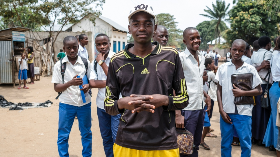 "Swedi stands with his former classmates in Uvira. He fled Burundi with his mother after two of his brothers were killed. Because of financial hardship, he cannot afford to go to school anymore and has to work instead. ""When I see the children going to school I feel bad,"" he says. ""My heart aches."""
