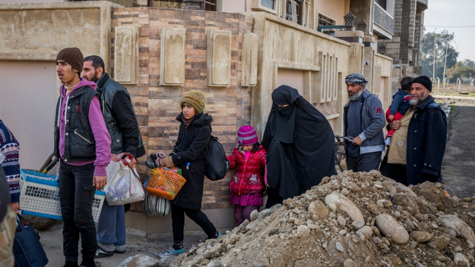 Iraqi families flee Al Thaqafa neighbourhood shortly after being liberated by the Iraqi military.