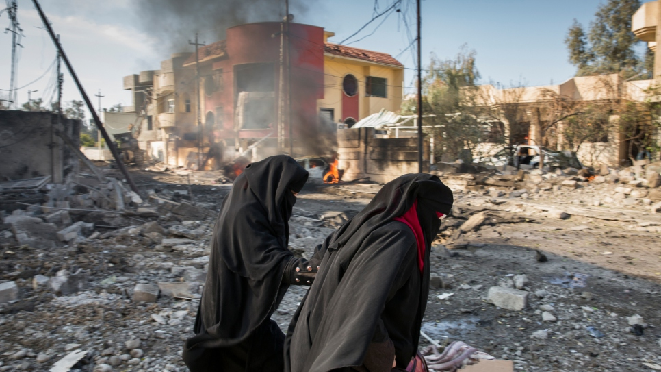 A family flees their destroyed home minutes after a suicide car bomber detonated his vehicle on the street outside in the Al Andalus neighbourhood of Mosul.