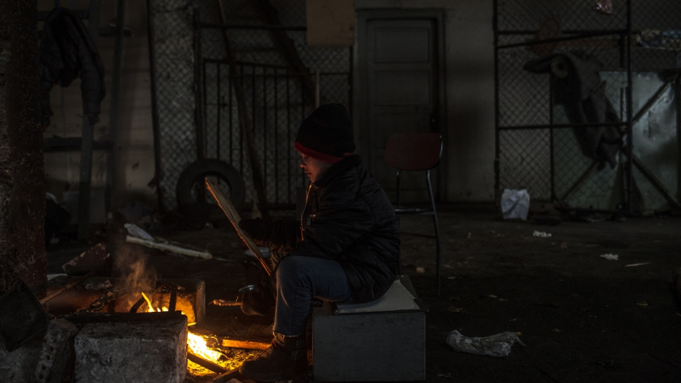 Aziz Jabarkheil, 8, sits by a fire to keep warm in sub-zero conditions in Belgrade. Aziz has not slept in a real bed in almost a year.