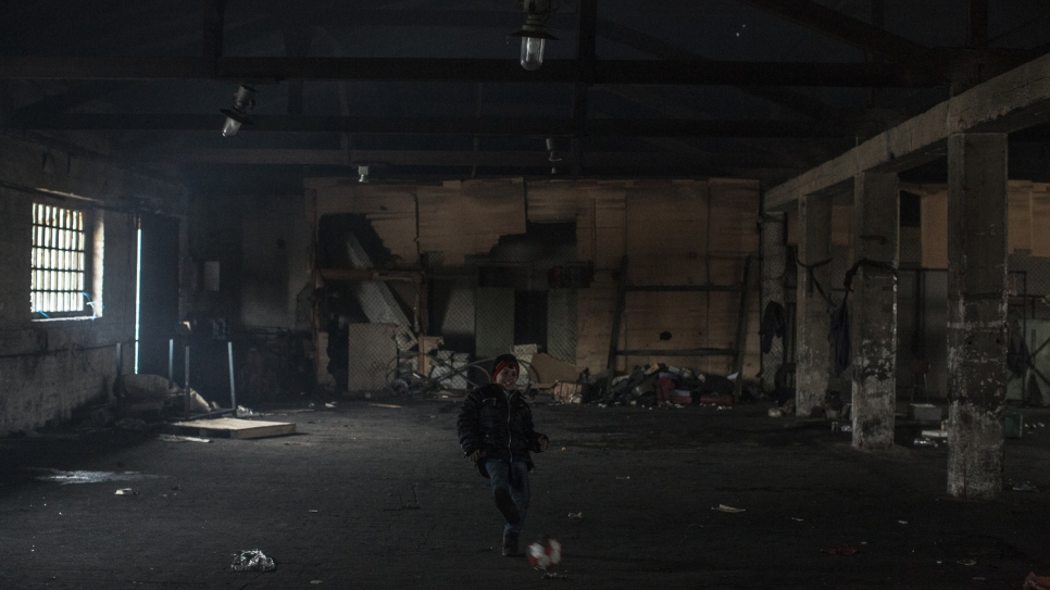 Aziz kicks around a deflated football to keep warm in sub-zero conditions in a Belgrade warehouse where he insists on sleeping despite efforts to persuade him and relatives to move to a government-run shelter.