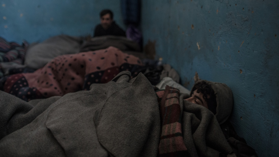 Afghan refugees wake up after a night sleeping under blankets in freezing conditions in a Belgrade warehouse.