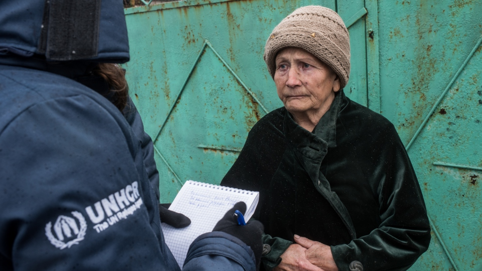 A UNHCR worker writes down 82-year-old Nelya's winter fuel needs in the village of Luhanske, Donetsk.