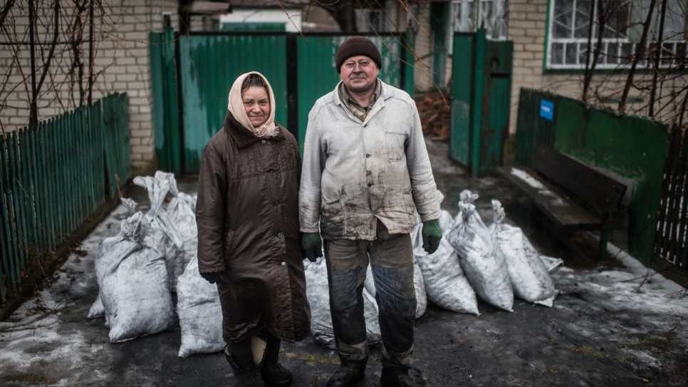 Anna, 68, and Victor, 67, stand in front of several bags of coal that will heat their homes in the village of Luhanske, Donetsk.