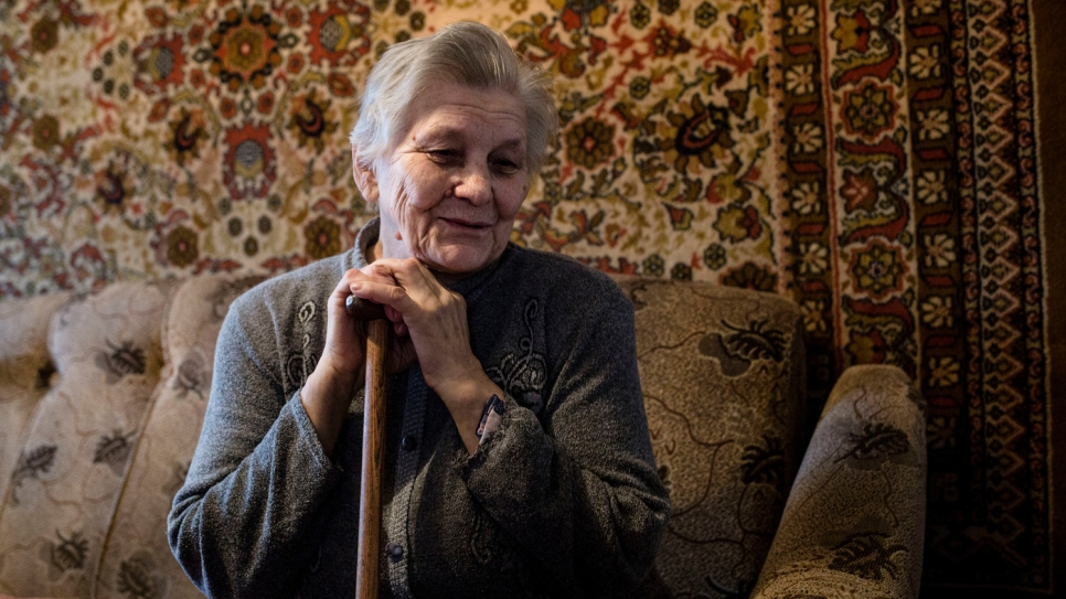 Hanna sits in her living room. She has stayed with her sick husband since the war began in eastern Ukraine in April 2014.