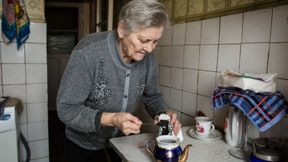 Hanna makes tea in her kitchen in Shchastya. Despite dangers and constant challenges, she and her sick husband Oleksiy have stayed on since the conflict began in April 2014.