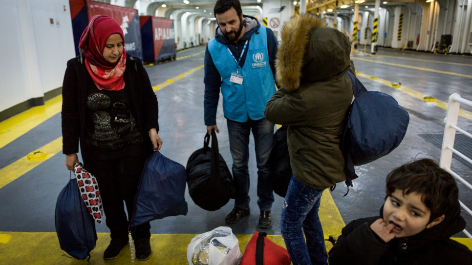 A UNHCR staff member helps Falak and her sons carry their bags onto a ferry bound for Athens.