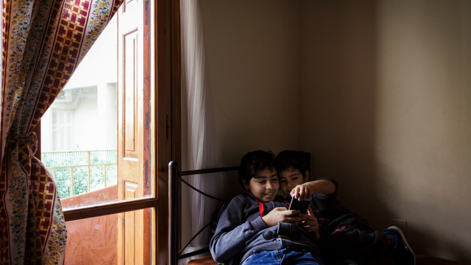 Samir watches cartoons on a cell phone with his younger brother.
