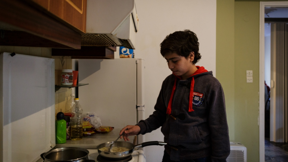 Fourteen-year-old Samir cooks in the kitchen of his family's shared accommodation.