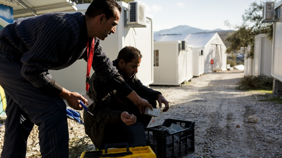 Mohamed (left) and his brother Mofeed, prepare electrical boxes, before wiring them into prefabricated houses at Kara Tepe accommodation facility.