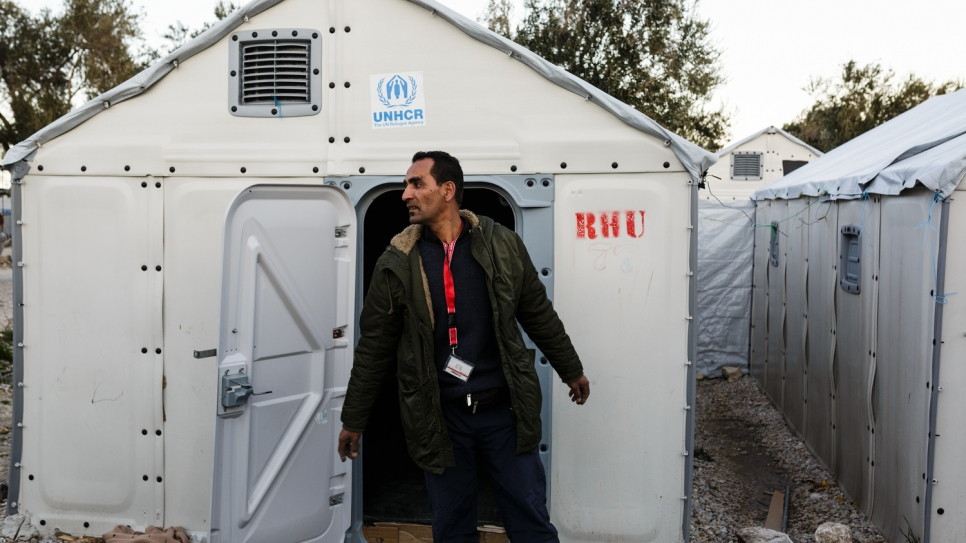 Mohamed stands outside a refugee housing unit at the Kara Tepe accommodation facility where he volunteers as an electrician along with his brother Mofeed.