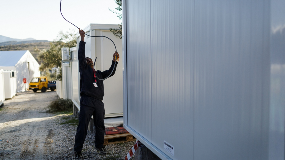 Mohamed installs electric cables at a newly installed prefabricated house, inside the Kara Tepe accommodation facility.
