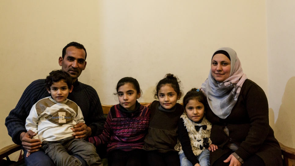 Mohamed and Maysoun pose for a portrait with their children, (left-to-right) Baraa, Alissar, Limar, and Elian inside the house given to the family by UNHCR.