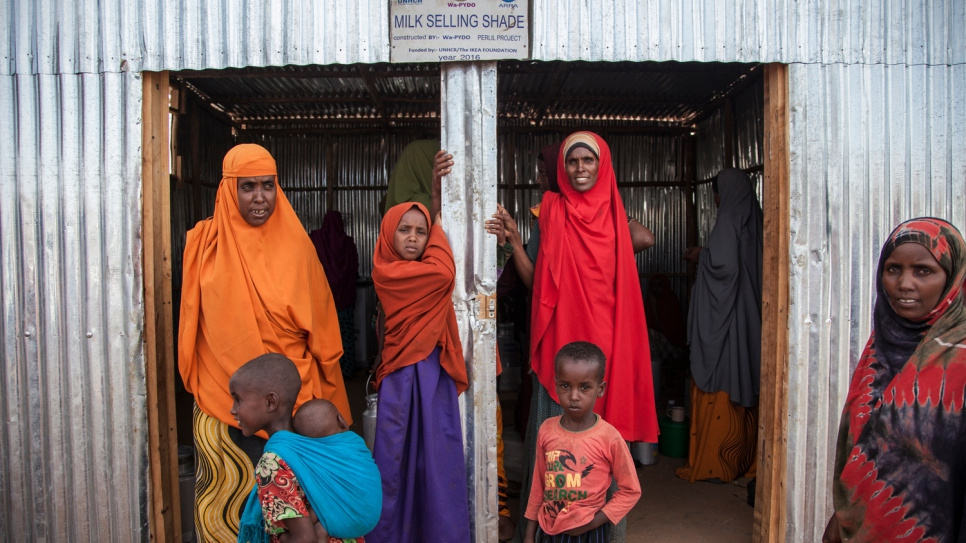"Somali refugee women stand outside the dairy cooperative after a long day. ""We are 20 women who have created a cooperative to sell milk and become self-reliant. We sell milk to refugees and the host community, and generate income to sustain our families."""