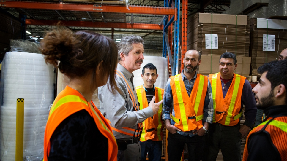 Jim Estill speaks with employees at the company warehouse.