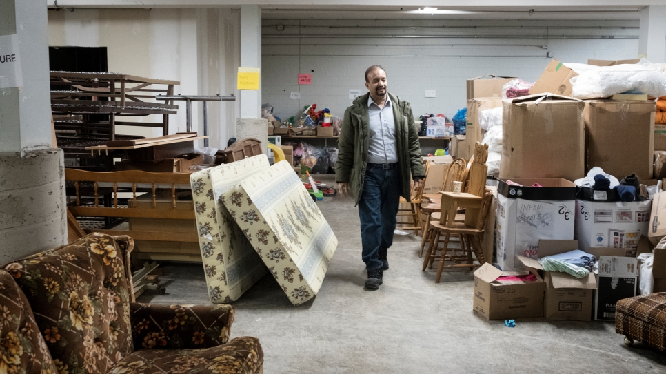 Muhammed Sayyed, president of the Muslim Society of Guelph, walks through the warehouse space used by volunteers helping to resettle Syrian refugees.