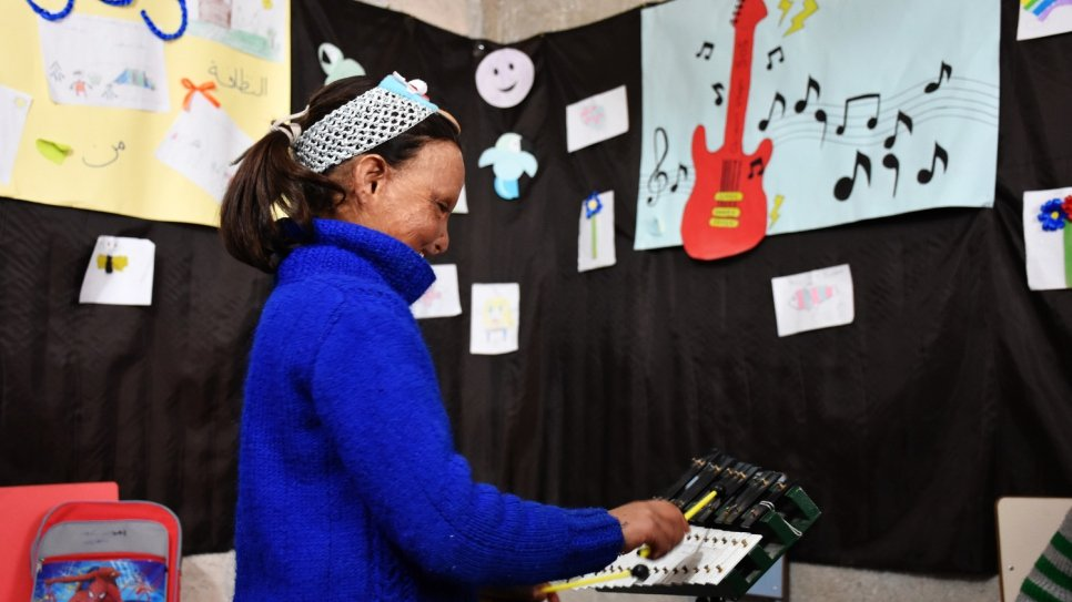 Wafaa plays music in a classroom at the temporary shelter, where she has finally been able to start her education and attend school for the first time.