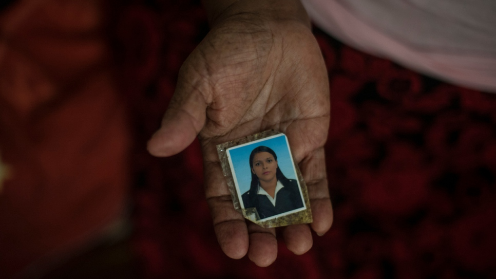 Maria holds a photo of her daughter Sara, who was killed by a gang at age 27.