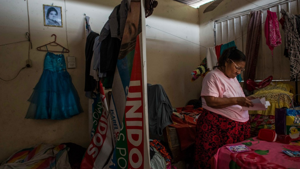 Maria looks at family photos in her room in southern Mexico. The dress hanging on the wall belonged to her great-granddaughter, Maria Luz, who was killed by a gang member in El Salvador.