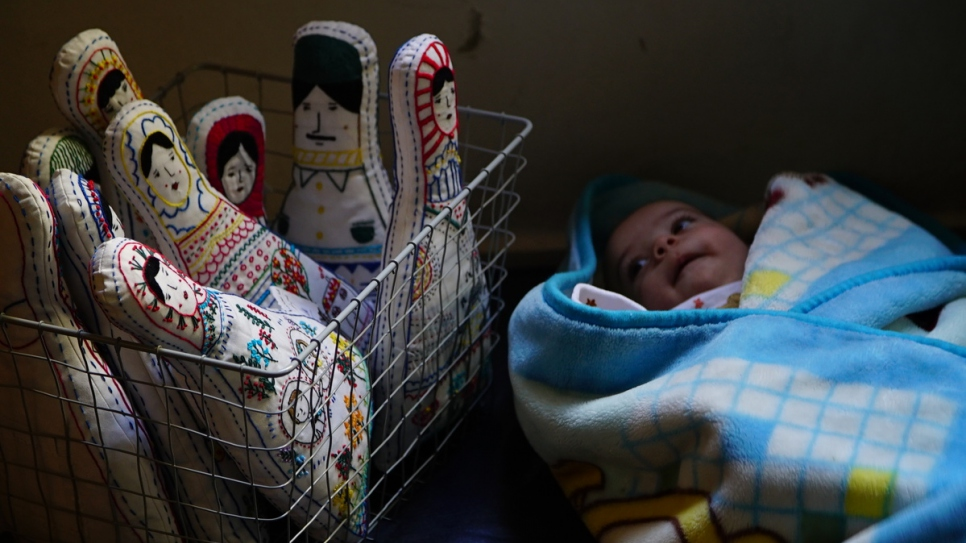 A newborn baby sleeps next to Amina's embroidered dolls.