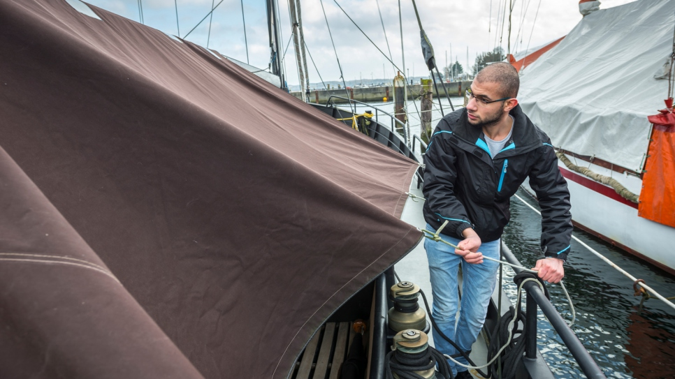 Yousef ties down a boat cover he repaired with his father Mohammed at the Kiel sailmaking company Coastworxx.