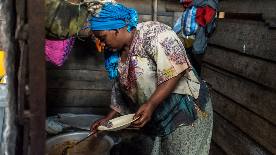 Odette serves up food in the kitchen of her restaurant in Goma.