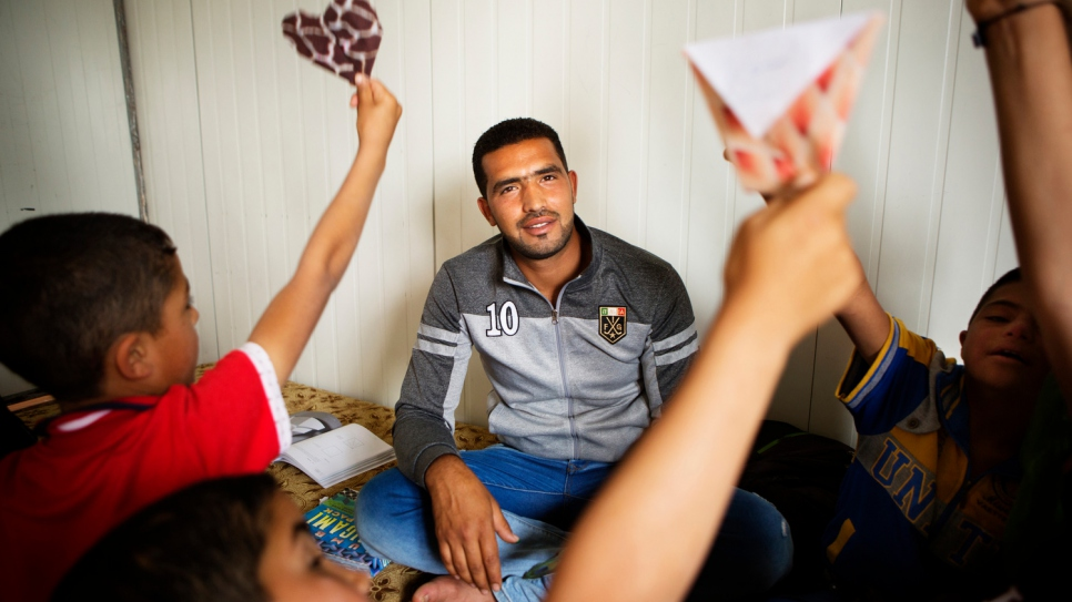Fadi works as a classroom assistant at a community centre funded by UNHCR.