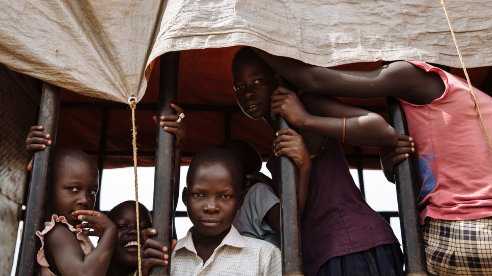 South Sudanese refugees look out of a truck before being transported to the recently established Imvepi settlement, at the Imvepi Reception Centre, Arua District, Northern Region, Uganda. The Imvepi settlement was opened in February 2017 to deal with the large influx of refugees from South Sudan.