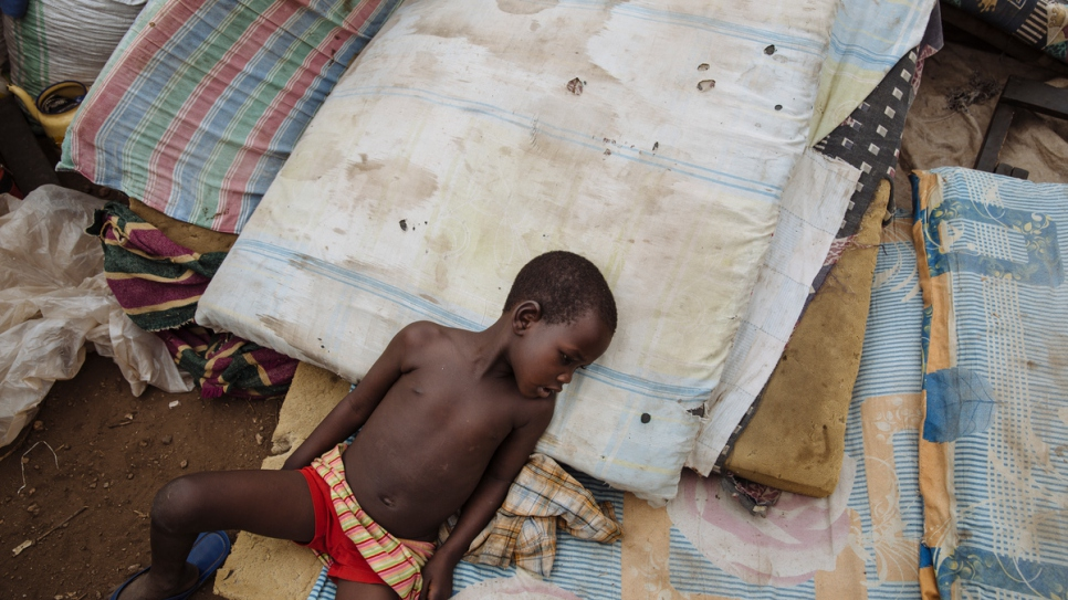 A South Sudanese refugee lies on mattresses placed on the ground at the Imvepi Reception Centre, Arua District, Northern Region, Uganda. The mattresses are just some of the personal items which refugees carried with them across the border into Uganda.