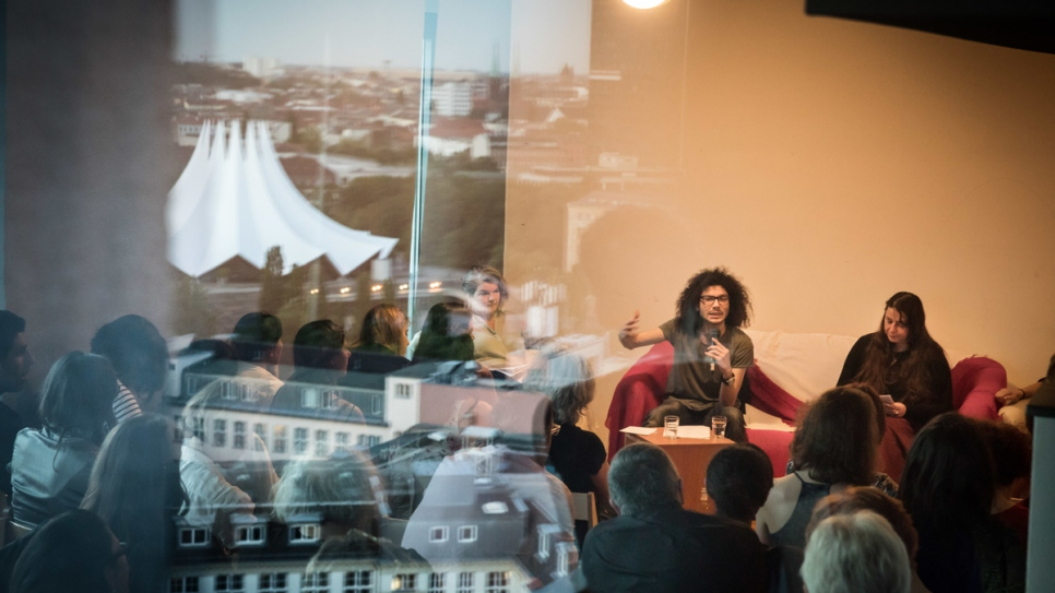 Syrian-Palestinian writer Ramy Al-Asheq talks at Muhannad's library in Berlin.
