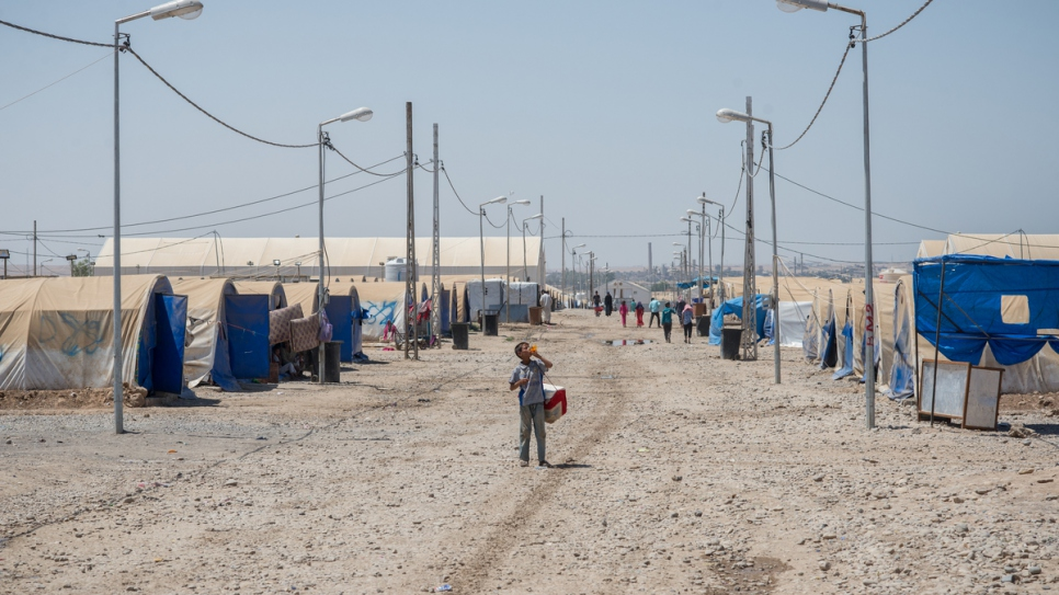 A young boy walks along a main road at Hammam Al-Alil camp.