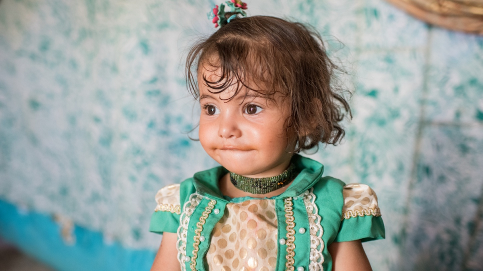 Bedoor, 2, plays in her tent at Hammam Al-Alil camp.