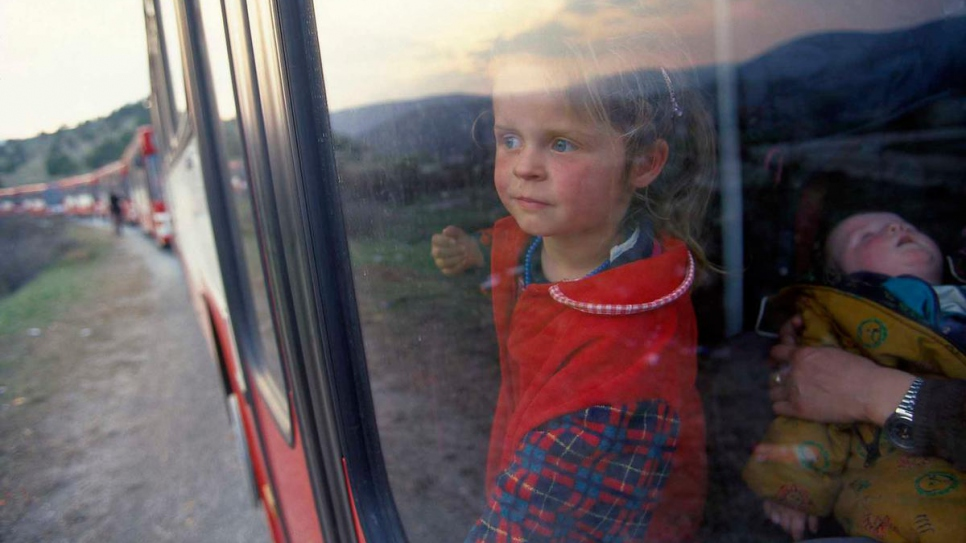 A young refugee from Kosovo* looks out the window of a train bound for Skopje airport. Her family 