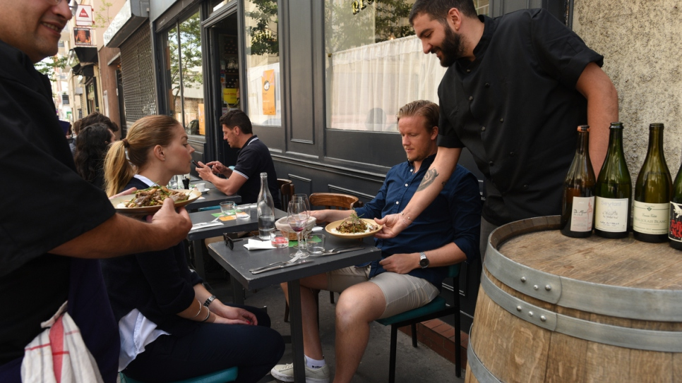 Syrian refugee chef Nabil Attar (far left) serves dishes with restaurateur Walid Sahed (far right) at Les Pantins restaurant in Paris.