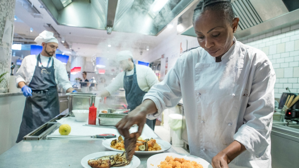 Rita, a refugee from the Democratic Republic of Congo, prepares a fish dish in the kitchen of Eataly in Milan.