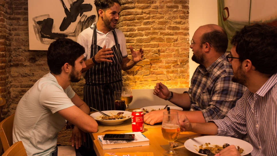 Refugee chef Mohammed greets customers at l'Artisan restaurant, in Madrid. Photo by Jane Mitchell.