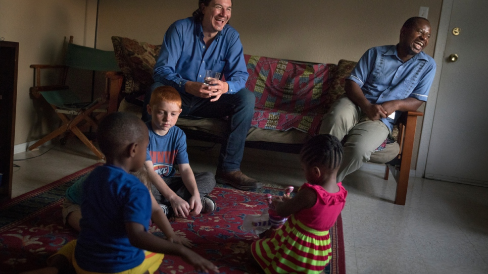 Cobi Cogbill, 31, (left) and Majidi, 36, hang out as their children play together at his house in Fayetteville, Arkansas. They have become best friends since meeting.