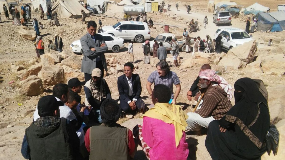 Adem Shaqiri (centre, blue check shirt) negotiates with landowners and authorities to ensure immediate access to deliver aid to 300 displaced families at an informal settlement in Khamir, Yemen, in February 2017.