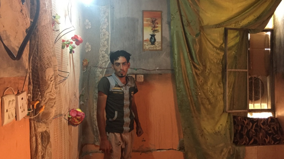 Ibrahim Khalil, a 25 year-old labourer and crane-driver, stands inside one of the damaged rooms in his house in Ramadi, Ira
