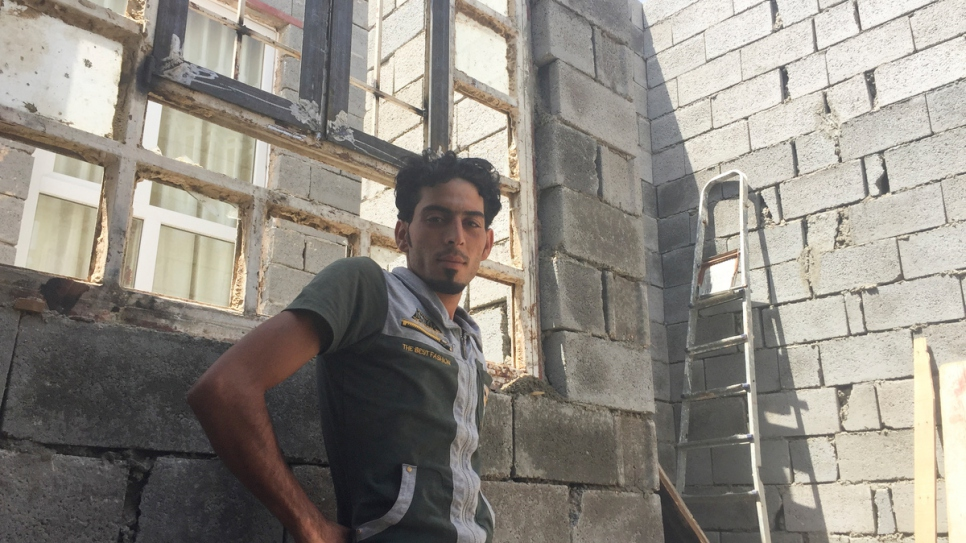 Ibrahim Khalil, a 25 year-old labourer and crane-driver,stands near a broken window in his house - the roof exposed to the sky.