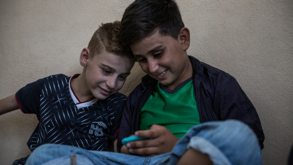 Yazidi boy Emad Tammo (left) watches video games on his cousin's cellphone as he counts down the days in Dohuk, Kurdistan Region of Iraq, before rejoining his mother in Canada.