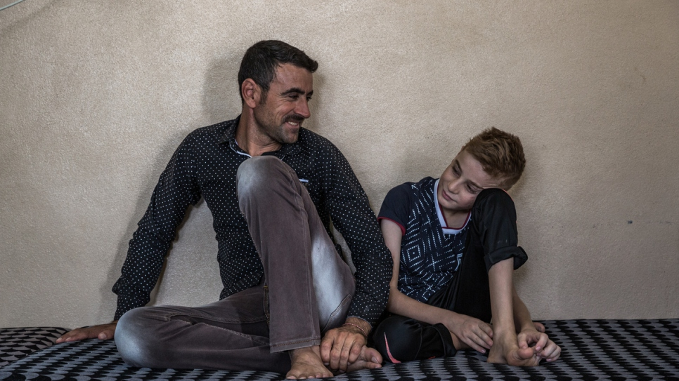 Hadi Tammo, 31, sits with his nephew Emad in a house in Dohuk, Kurdistan Region of Iraq.
