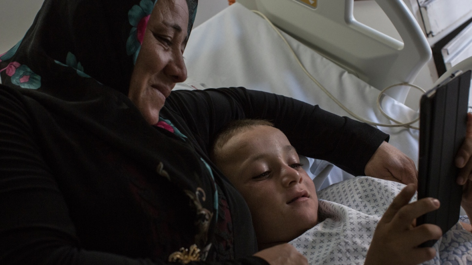 Issam looks at an iPad with his mother Badriyeha before undergoing surgery at the Sacre Coeur Hospital.