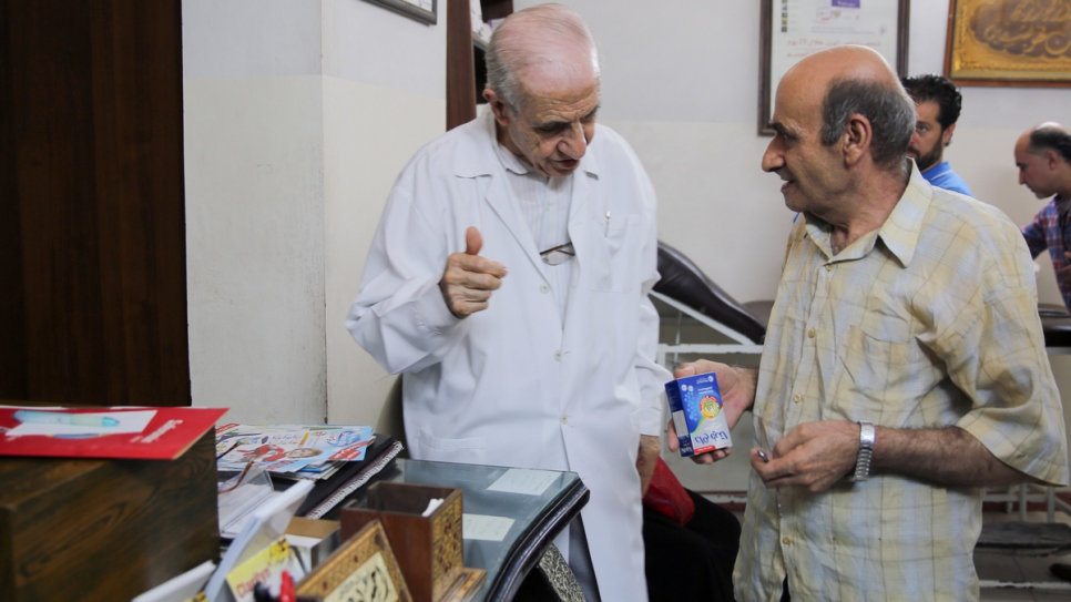Dr. Ihsan Ezedeen speaks to a patient at his clinic in Jaramana City, near Damascus. Over a period of seven years he is estimated to have provided medical care to 100,000 internally displaced people.