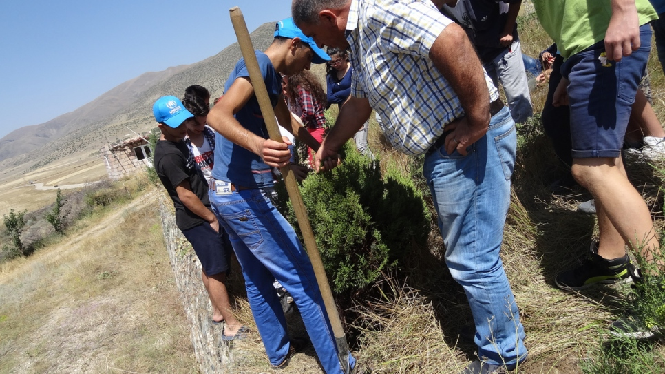 Displaced and refugee youth gather to plant trees.