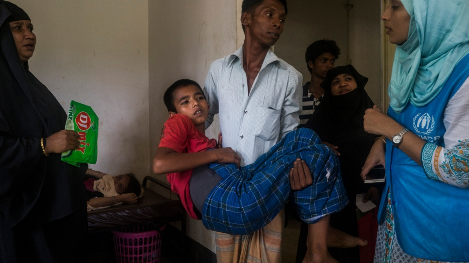 Hubaib, 12, a Rohingya refugee from Myanmar is carried into a room at a UNHCR funded Refugee Health Unit in the Kutupalong Refugee Camp in Kutupalong, Bangladesh. Hubaib was shot in the back and his father was shot and killed.
