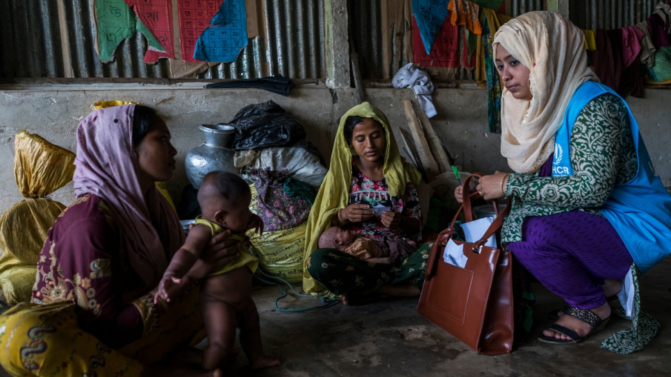 Hosna Ara Begum, 30, a UNHCR staff member talks with newly arrived Rohingya refugees as they shelter in a College Hill Primary School in the Kutupalong Refugee Camp.